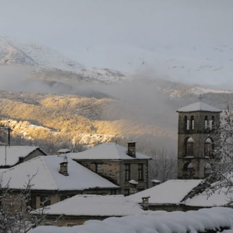 snow covered slate roofs in dilopho village, central zagori